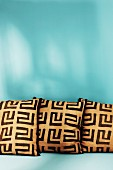 Three cushions with graphic patterns against turquoise background