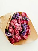 Strauß aus Rosen und Strandflieder in Packpapier
