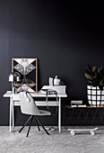Gray chair and desk against black wall