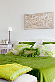 Green bedlinen and ornate scatter cushions on bed