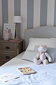 Teddybär aus Stoff sitzt auf dem Bett im blau-weißen Schlafzimmer