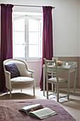 Armchair and desk below window in vintage-style bedroom