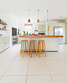 Bar stools at island counter in modern country-house kitchen