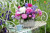 Basket with early-summer perennials arrangement on garden bench
