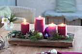 Fast Advent wreath made of 4 candles on wooden bowl, Pinus branches
