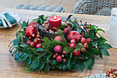 Red candle made of Ilex and conifers branches