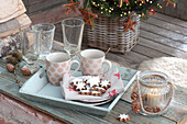 Plate with cinnamon stars and cups on tray, glasses, lantern