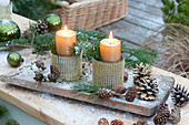 Candle decoration in goblets with gold decor on wooden board in the first snow