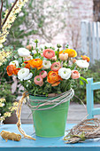 Lush ranunculus (ranunculus) bouquet in the green metal bucket