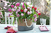 Lush bouquet of mixed Tulipa (tulip) in braided bag
