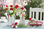 Ranunculus bouquets in watering cans and glass bowl
