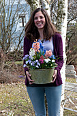 Woman carrying pot with Hyacinthus, Viola cornuta 'Lavender Blush'