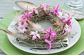 Small hay wreath with flowers of Hyacinthus and feathers