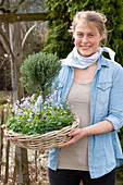 Woman carrying basket bowl with thymus vulgaris (thyme) as stems