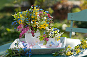 Colorful spring bouquets in jug on wooden tray