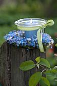Small preserving jar as lantern in wreath from Myosotis