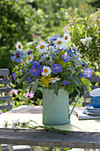 Early summer flowering perennials bouquet in a green pot