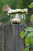 Small wreath made of Convallaria majalis (lily of the valley) with feather