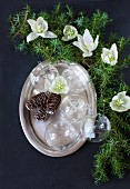 Glass Christmas-tree baubles and pine cones on silver platter next to green conifer branches and hellebore flowers