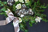 Glass Christmas-tree baubles, green conifer branches, hellebore flowers and satin ribbon