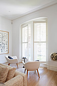 Two armchairs in the bright room in front, windows with shutters