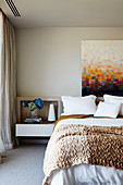 Picture with painted pixels over the bed with knitted blanket