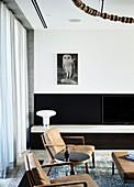 Armlehnstühle mit Lederpolsterung vor Fernsehschrank im Wohnzimmer