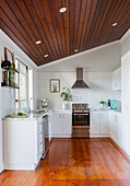 White kitchen under the sloping ceiling with covered ceiling