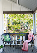 Two round chairs and a filigree table on the veranda