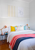 Pictures on a decorative strip above the bed with colorful pillows and plaids