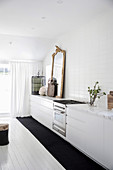 White kitchenette with antique gold frame mirror and cage, white wooden floorboards