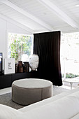 White sofa and ottoman, sideboard with antique vessels and dark curtain in front of the patio door
