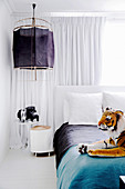 Bedroom with soft toy, bedside table and hanging lamp in front of white curtain