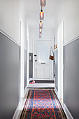 Patterned runner on floor of hallway with two-tone walls in period apartment