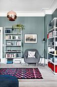 Schlichte Regale an petrolblauer Wand im Wohnzimmer