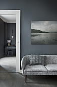 Retro sofa below gloomy landscape photograph on grey wall