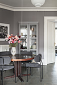 Grey upholstered chairs at round table in room with grey walls