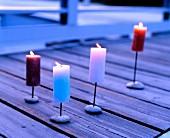 Lit pillar candles on wooden deck
