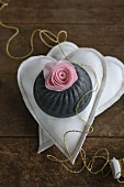 Silk flower and bundt tin on two fabric hearts
