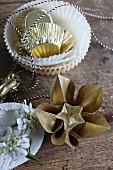 Goldfarbene Origamiblume neben Muffinförmchen und Bäckergarn