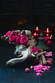 Pink double roses on twisted root wood with candles in background