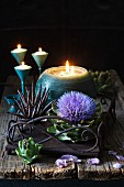 Artichoke flower and spherical candle on rusty metal tray
