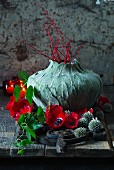 Red and grey arrangement around vase wrapped with leaves