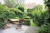 Garden furniture on terrace in lush green garden