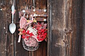 Viburnum berries and sugar in wire basket hung on wooden wall