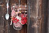 Schneeballbeeren und Zucker im Drahtkorb an Holzwand