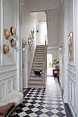 Treppe im Eingang mit Schachbrettboden und Kasettenwänden