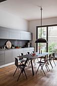 Moderne Essgruppe in großer grauer Einbauküche mit Balkon