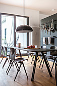 Black, modern dining table in front of hook rails mounted on grey wall