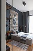 Schlafzimmer in Grautönen mit einem Bild auf Brettern überm Bett